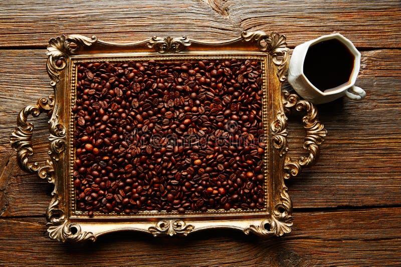 Кофейная чашка и фасоли на винтажном золотом подносе стоковые фотографии rf