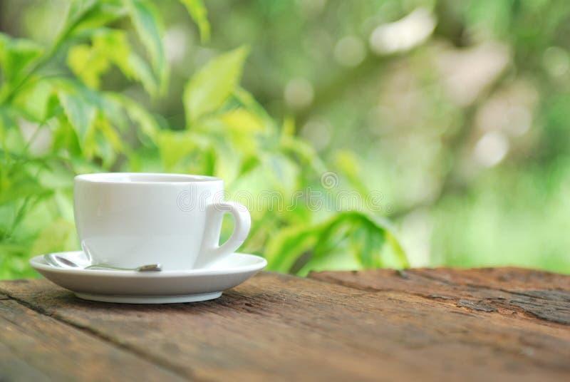 Кофейная чашка на деревянной таблице с зеленой предпосылкой стоковые изображения rf