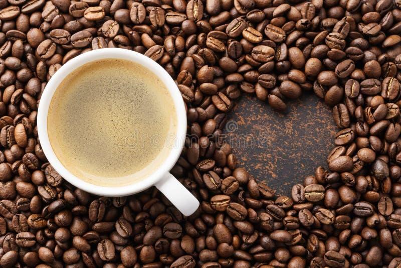 Кофейная чашка на зажаренных в духовке кофейных зернах и рамке сердца форменной стоковое фото rf