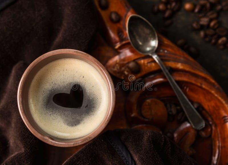 Кофейная чашка при форма сердца сделанная пены на старом колониальном деревянном столе, взгляд сверху стоковая фотография