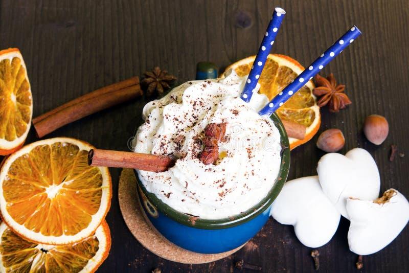 Кофейная чашка рождества с взбитой сливк, циннамоном, бурым порохом, анисовкой, высушила печенья апельсина и пряника стоковая фотография