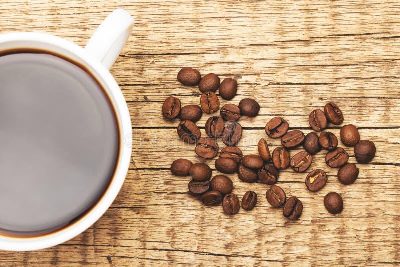Кофейная чашка с зажаренными в духовке кофейными зернами приближает к ей Фильтрованное изображение: влияние обрабатываемое кресто стоковые изображения rf