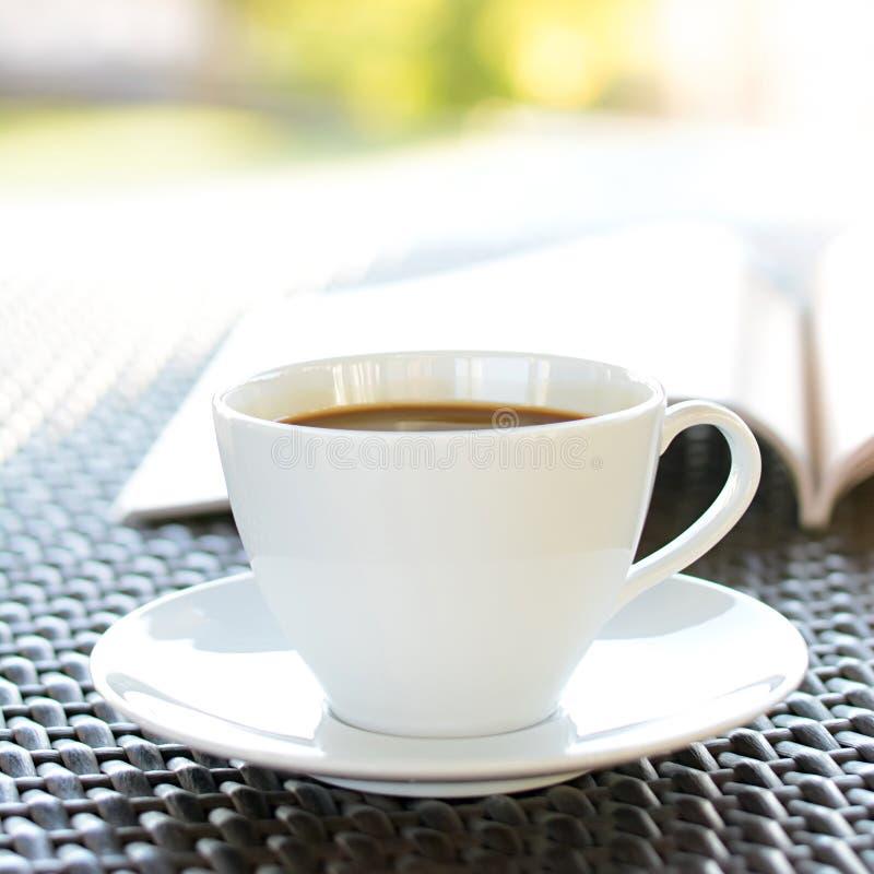 Кофейная чашка с книгой на плетеной таблице стоковое фото