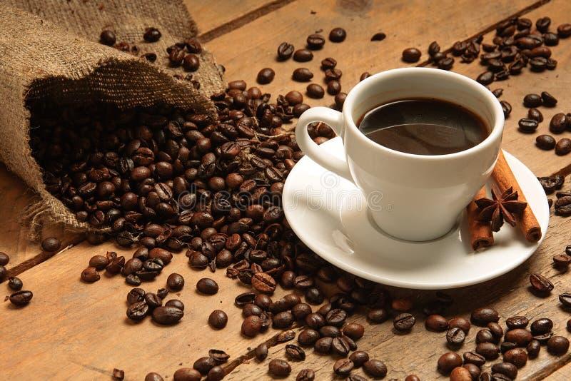Кофейная чашка с кофейными зернами круассаном, циннамоном на bagging и древесиной стоковые фото