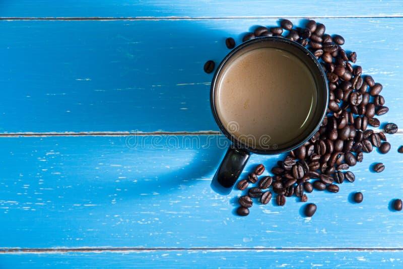 Кофейная чашка с кофейными зернами на голубой деревянной предпосылке стоковые фотографии rf