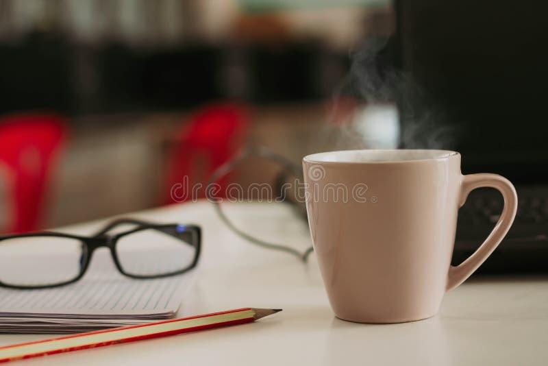 Кофейная чашка с ручкой циннамона на деревянной таблице стоковое изображение