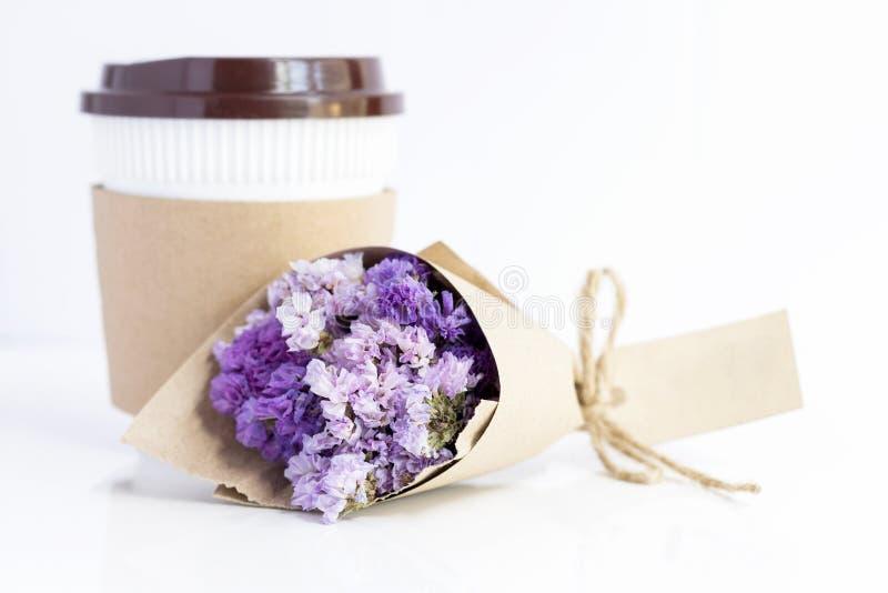 Кофейная чашка с фиолетовым букетом цветка statice на белой таблице стоковое фото