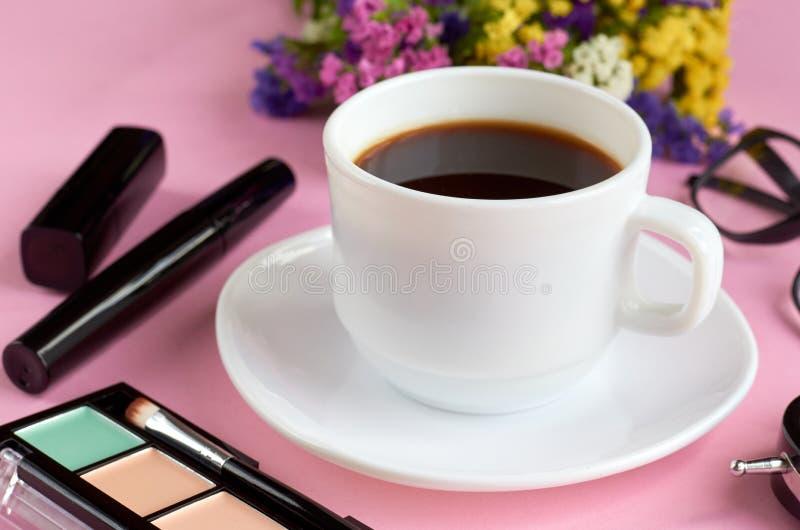 Кофейная чашка, цветки, тушь и стекла на розовом составе предпосылки стоковые фото