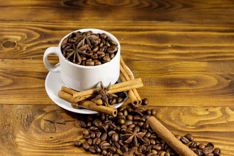 Кофейные зерна в белых чашке, ручках циннамона и анисовке звезды на деревянном столе стоковая фотография rf