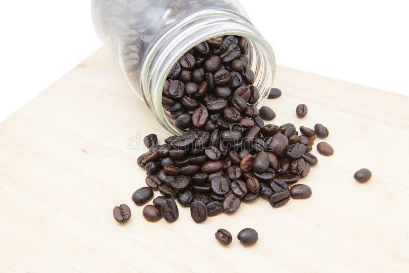 Кофейные зерна в бутылке на деревянном блоке стоковое изображение