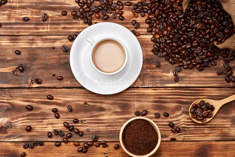 Кофейные зерна в ложке и чашке горячего напитка стоковые фотографии rf
