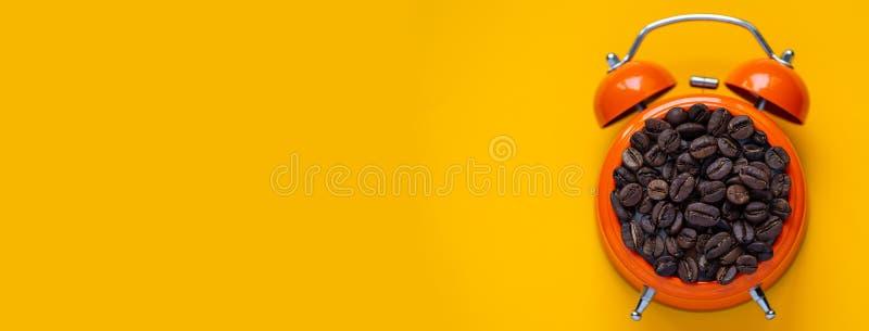Кофейные зерна в оранжевом будильнике на желтой предпосылке стоковое фото rf