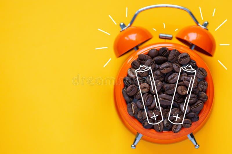 Кофейные зерна в оранжевом будильнике на яркой желтой предпосылке стоковое изображение rf