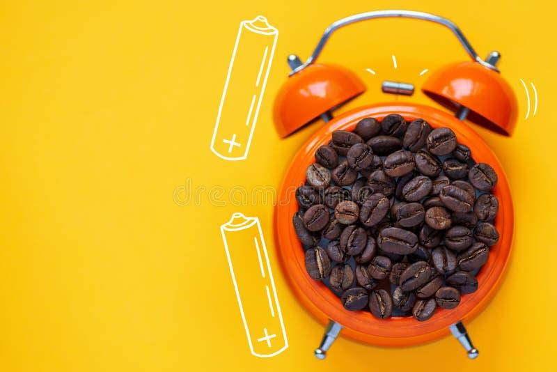Кофейные зерна в оранжевом будильнике на яркой желтой предпосылке стоковая фотография rf
