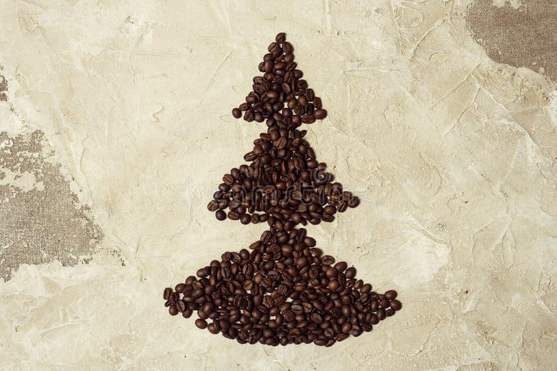 Кофейные зерна в сердце формируют на тканях предпосылки джута стоковое изображение