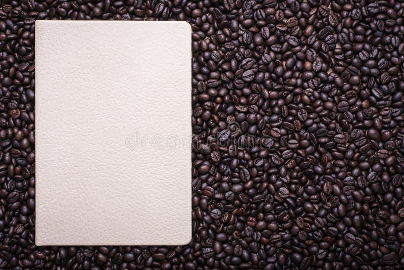 Кофейные зерна и блокнот на деревянной предпосылке стоковое изображение
