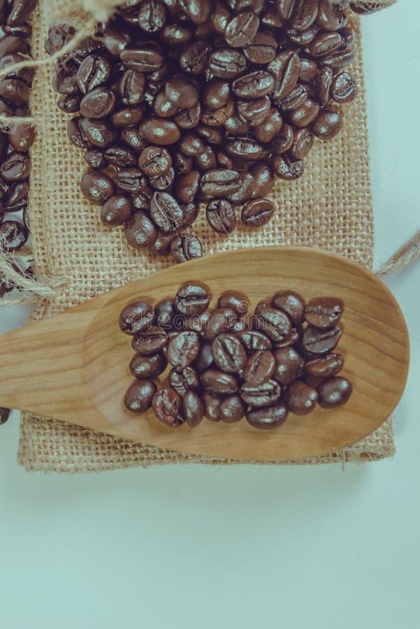 Кофейные зерна и деревянная ложка на мешке отделывают поверхность стоковое фото rf