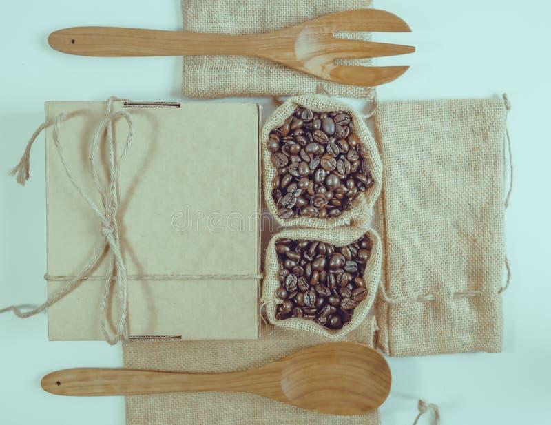 Кофейные зерна и деревянная ложка на мешке отделывают поверхность стоковые изображения rf