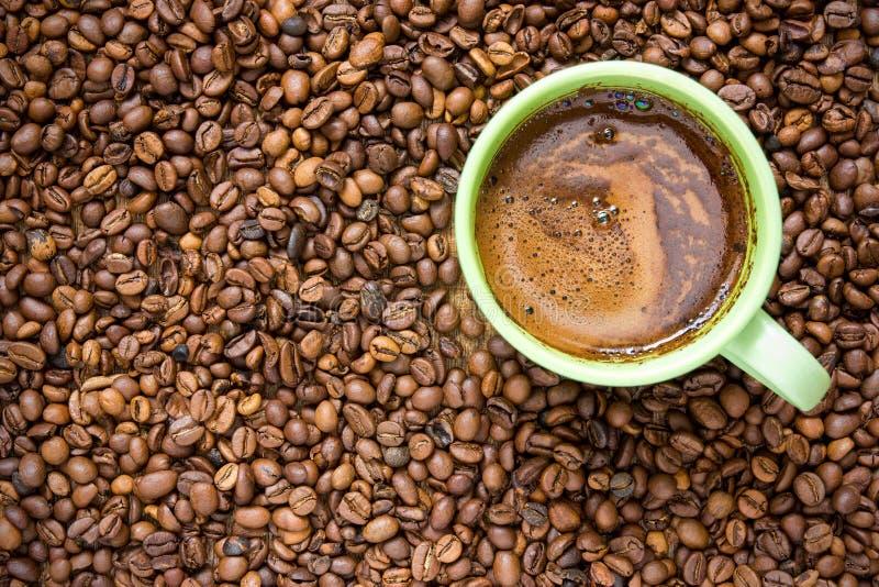 Кофейные зерна и зеленая чашка стоковые изображения rf