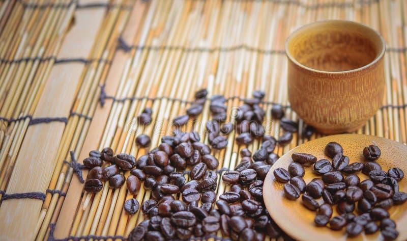 Кофейные зерна и кофейная чашка установили на бамбуковую деревянную предпосылку сфокусируйте мягко стоковое изображение