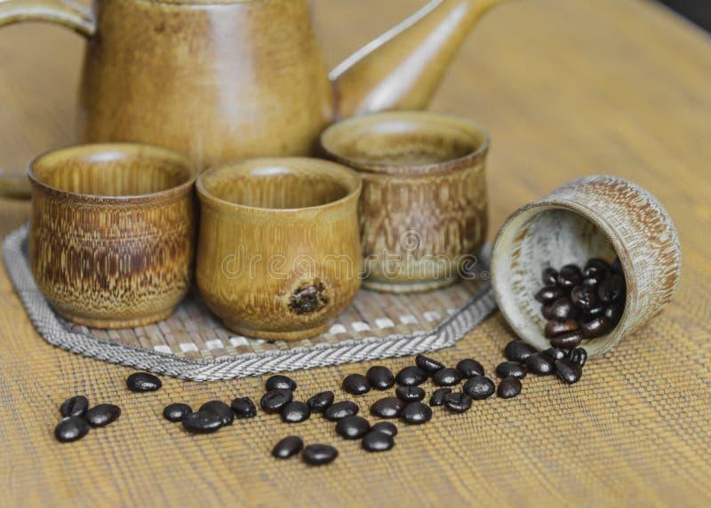 Кофейные зерна и кофейные чашки установили на деревянную предпосылку сбор винограда типа лилии иллюстрации красный (мягкий фокус) стоковые изображения