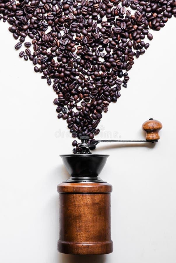 Кофейные зерна и ретро деревянный точильщик на белой предпосылке стоковые изображения rf
