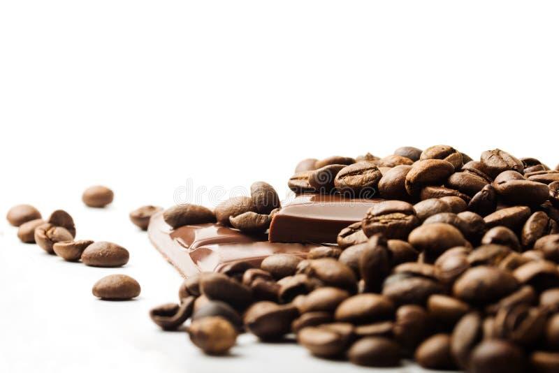 Кофейные зерна и части шоколада на белизне стоковая фотография