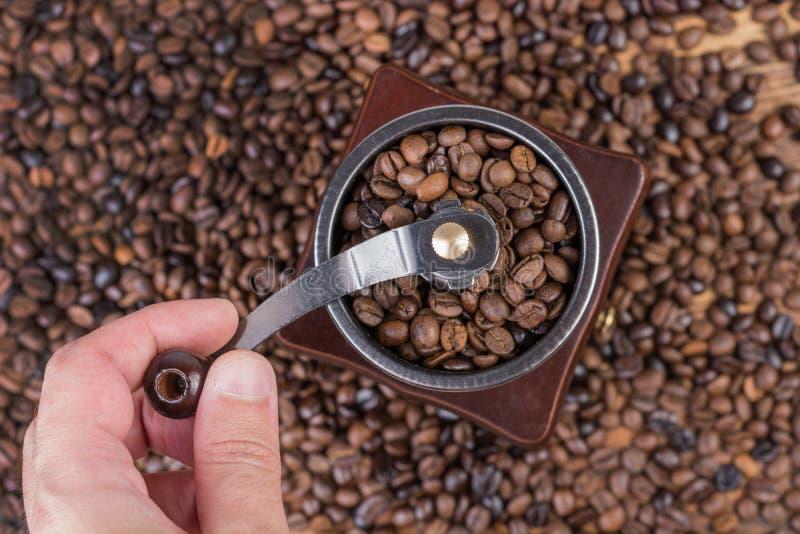 Кофейные зерна мужской руки меля в старой ретро мельнице кофе и зажаренные в духовке кофейные зерна в предпосылке стоковое фото rf