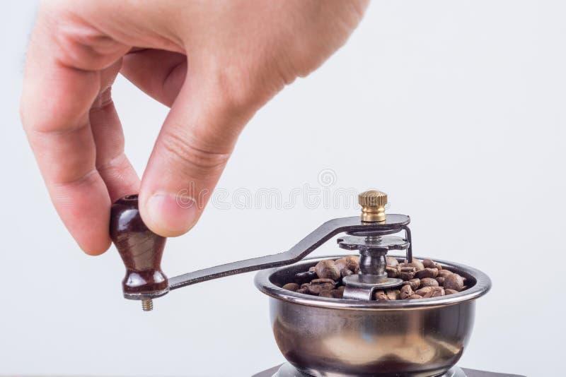 Кофейные зерна мужской руки меля в старой ретро мельнице кофе на белой предпосылке стоковая фотография