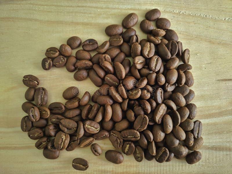 Кофейные зерна на деревянной предпосылке текстуры стоковые фото