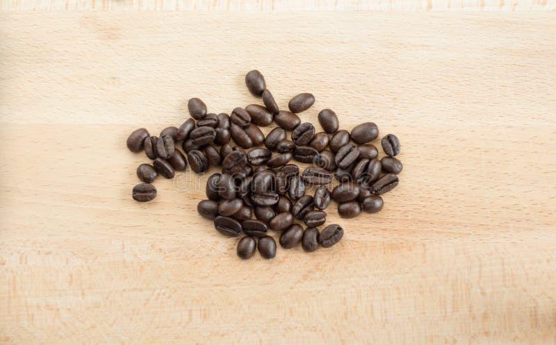 Кофейные зерна на деревянной предпосылке стоковые изображения