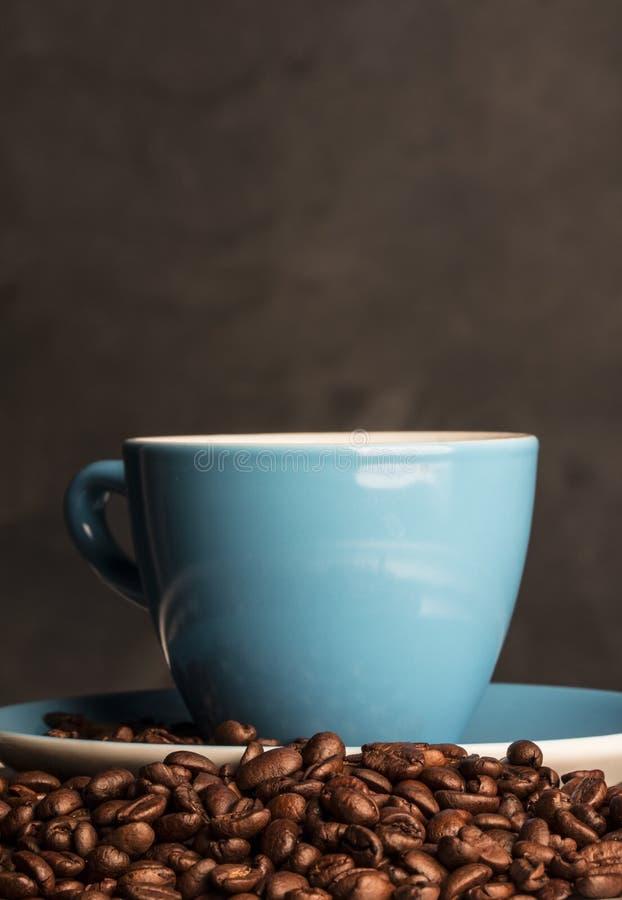 Кофейные зерна с голубой чашкой стоковая фотография rf