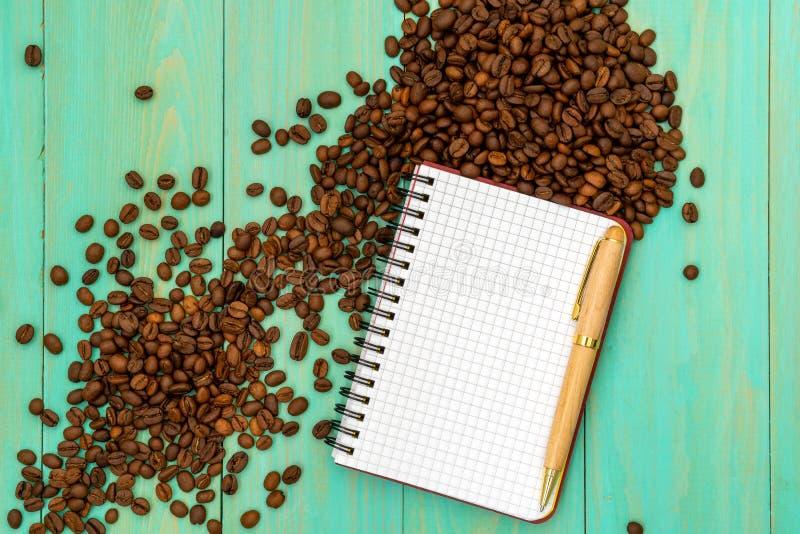 Кофейные зерна с открытой тетрадью для примечаний стоковые изображения rf