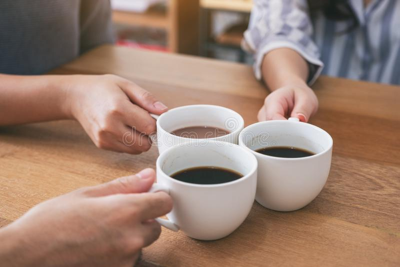 Кофейные чашки людей держа и clinking для того чтобы выпить на деревянном столе стоковая фотография