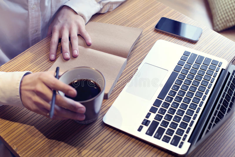 Кофе бизнесмена выпивая и работа на портативном компьютере, мобильном телефоне, пишущ бизнес-план, нося белая рубашка стоковое фото rf