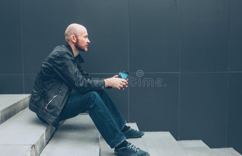 Кофе взрослого лысого бородатого человека выпивая от бумажного стаканчика и сидеть в лестнице на улице города стоковые фото