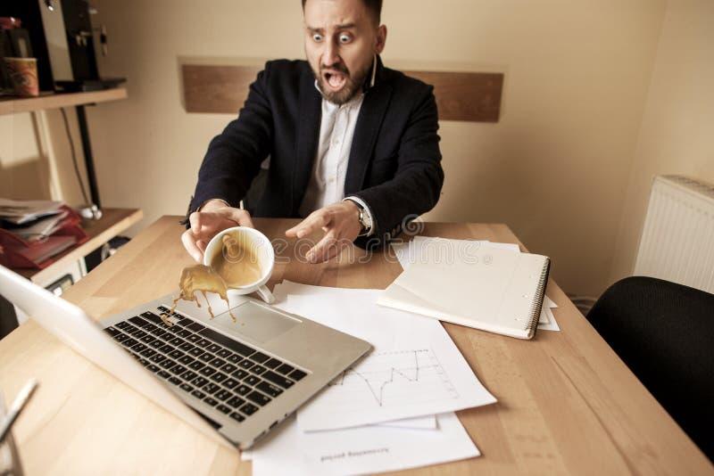 Кофе в белой чашке разливая на таблице в рабочем дне утра на таблице офиса стоковое изображение