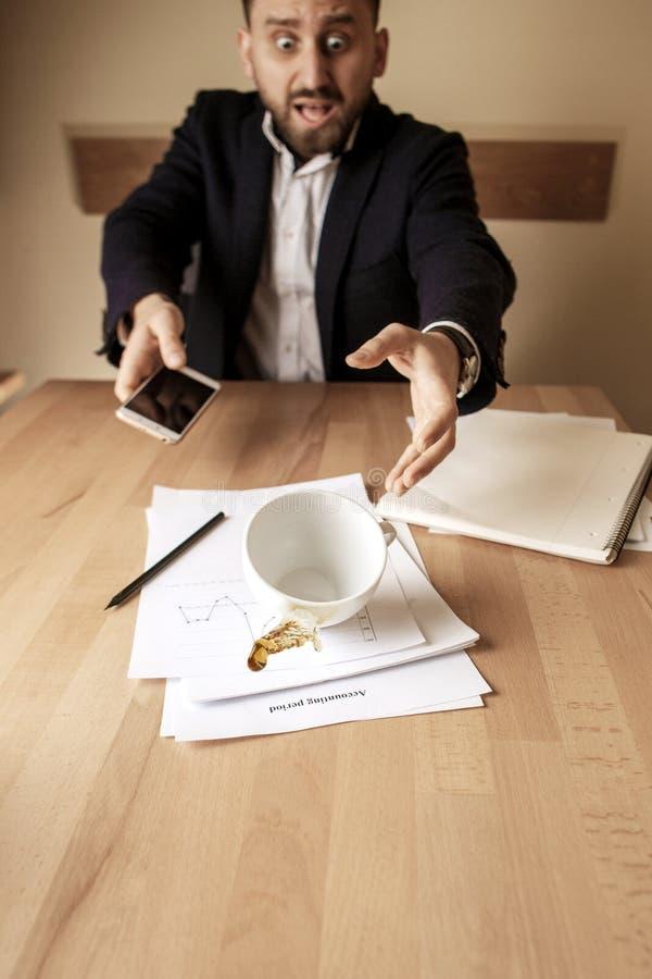 Кофе в белой чашке разливая на таблице в рабочем дне утра на таблице офиса стоковая фотография