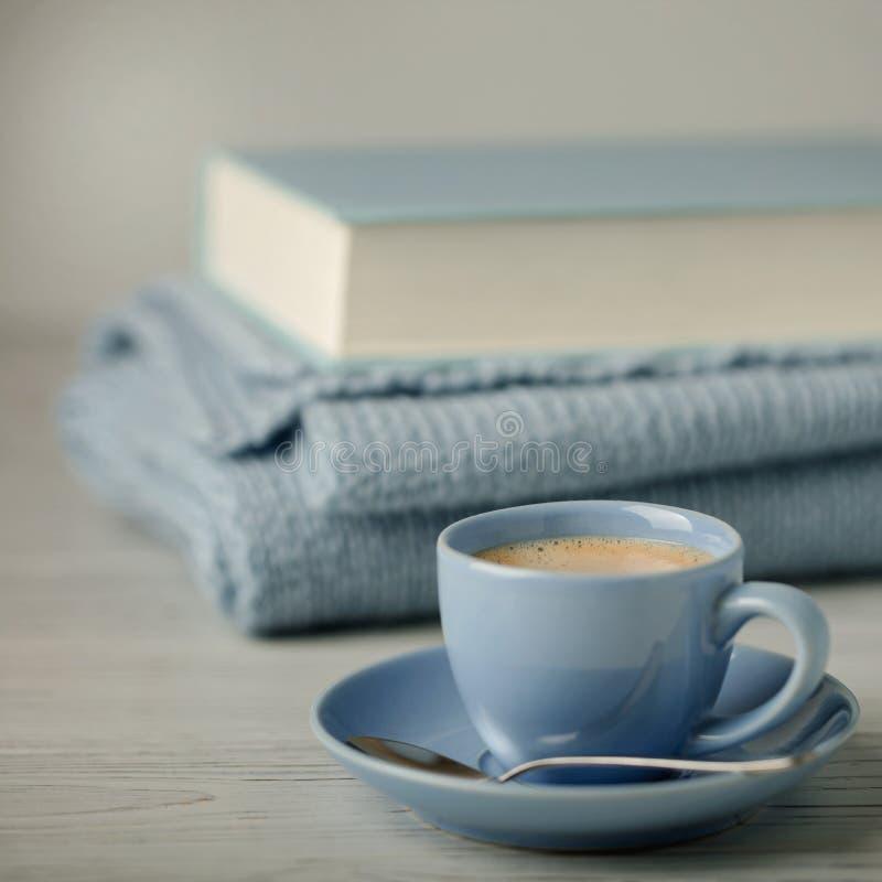 Кофе в свете - голубые чашка и книга в голубой вязке с knitt стоковая фотография rf