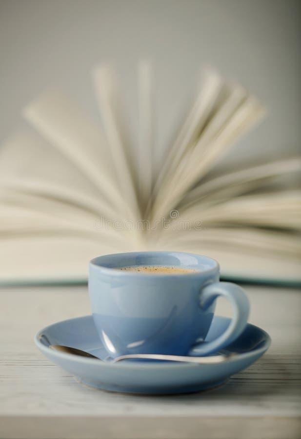 Кофе в свете - голубые чашка и книга в голубой крышке на деревянном ба стоковое изображение