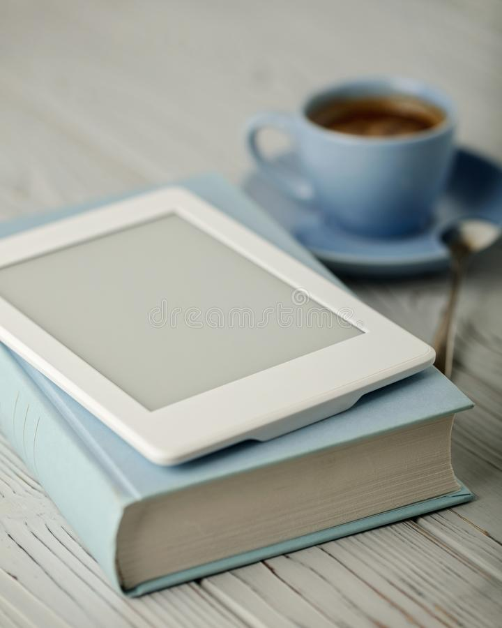 Кофе в свете - голубые чашка и книга в голубой крышке с электрическим стоковые фото