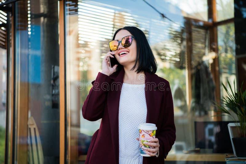 Кофе в улице, на открытом воздухе конец женщины красоты выпивая вверх по портрету моды, женщине офиса, времени захода солнца, дет стоковое изображение