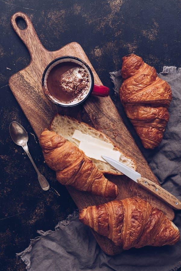 Кофе завтрака горячий и свежие круассаны с маслом на деревянной разделочной доске, темной деревенской предпосылкой Взгляд сверху, стоковая фотография