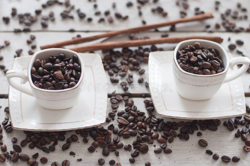Кофе, зерна, чашка, белизна, предпосылка, дерево, душистый кофе, ручки циннамона, стоковая фотография