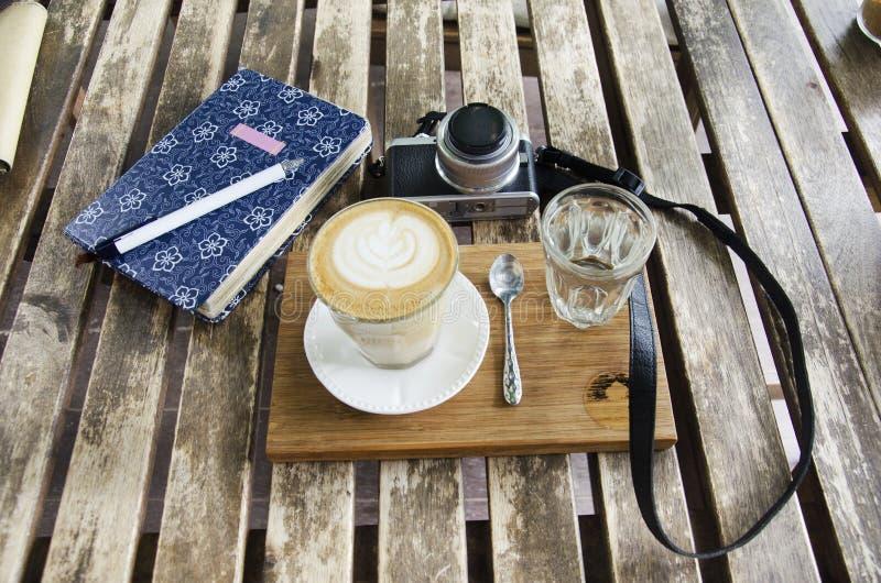 Кофе искусства Latte горячий с блокнотом и камерой блоггера путешественников стоковое изображение rf