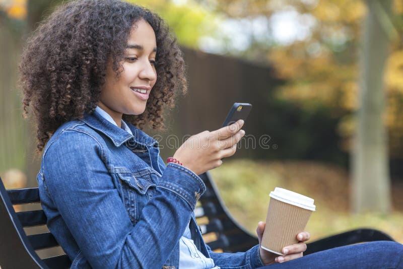 Кофе и отправка СМС Афро-американской женщины подростка выпивая стоковая фотография rf