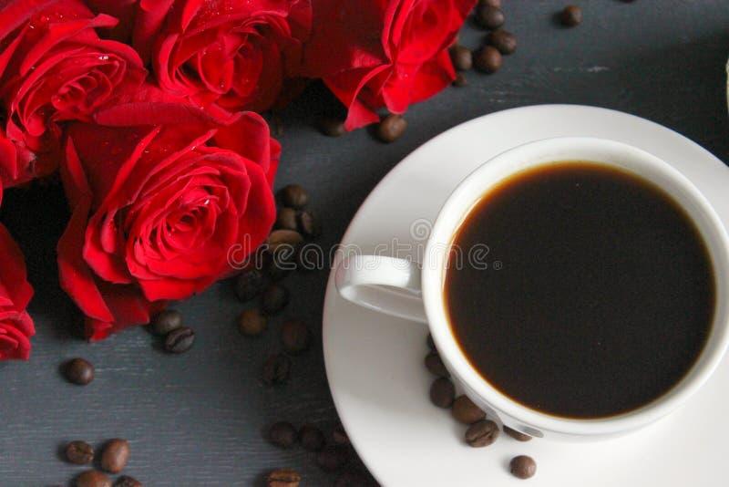 Кофе и розы, натюрморт Черный кофе в белой чашке с поддонником на таблице, букете красных роз стоковая фотография