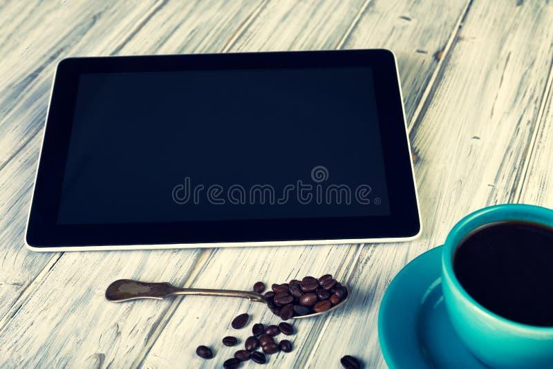 Кофе и таблетка на таблице стоковое фото