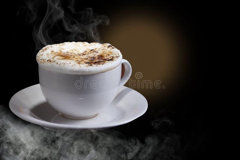 Кофе капучино или Latte Кофе Latte с пеной взбрызнутой с зернами карамельки коричневыми, в белой чашке, изолированной в темных те стоковые фотографии rf