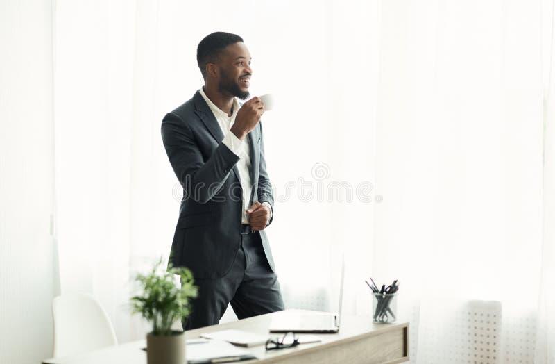 Кофе красивого Афро-американского бизнесмена выпивая около окна в офисе стоковое изображение rf